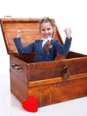 Little girl sitting in chest — Stock Photo