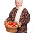 Senior woman with basket of apples  — Stock Photo