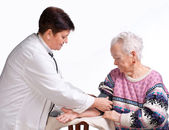 Elderly doctor and patient. Measuring pressure. — Stock Photo