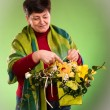 Beautiful senior woman with bouquet of flowers — Stock Photo #21504077
