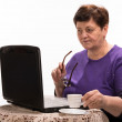 Mature woman with  glasses working on computer with cup of coffe — Stock Photo