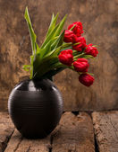 Beautiful red tulips in black vase — Stock Photo