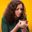 Stock Photo: Curly woman with a cup of tea or coffee