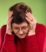 Mature woman suffering from a headache — Stock Photo