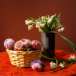 Easter eggs in basket and snowdrops in vase — Stock Photo