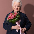 Senior woman with a bunch of flowers — Stock Photo #22294263