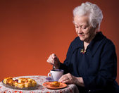 Old woman enjoying tea cup with apple pie — Stock Photo