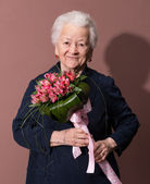 Senior woman with a bunch of flowers — Stock Photo