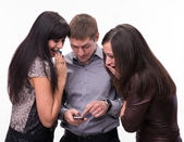 Group of surprised looking at a cell phone — Stock Photo