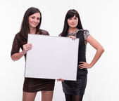 Portrait of two young women with billboard — Stock Photo