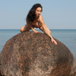 Young nude woman kneeling on a rock against the sea — Stock Photo