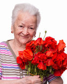 Old woman with bunch of poppies — Stock Photo