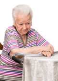 Pensive old woman sitting at the table — Stock Photo