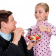 Stock Photo: Grandmother feeds strawberry to her granddaughter