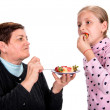 Grandmother feeds strawberry to her granddaughter — Stock Photo