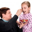 Grandmother feeds strawberry pie to her granddaughter — Stock Photo