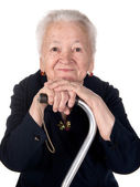 Portrait of smiling old woman sitting with a cane — Stock Photo