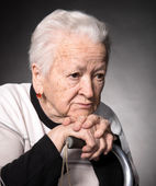 Portrait of old woman sitting with a cane — Stock Photo