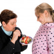 Stock Photo: Grandmother feeds strawberrypie to her granddaughter
