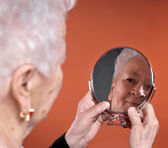 Portrait of old woman looking into a mirror — Stock Photo