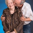 A grown son kissing his aging mom — Stock Photo