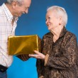 A grown son and aging mom with present box — Stock Photo
