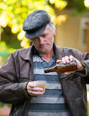 Drunk man with bottle of beer and glass — Stock Photo