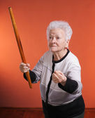 Old angry woman threatening with a rolling pin — Stock Photo