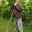 Stock Photo: Poorsad farmer with hoe
