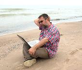 Defter ile sahilde oturan yaşlı işadamı — Stok fotoğraf