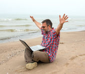 Emotional businessman with laptop on the beach — Stock Photo
