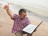 Emotional businessman with laptop on the beach — Stockfoto
