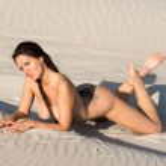 Nude woman sunbathing on the beach — Stock Photo