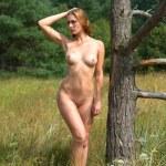 Nude woman posing near an old dry tree — Stock Photo