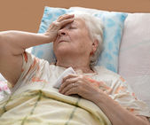 Senior woman lying at bed — Stock Photo