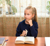 Schoolgirl studying and reading book at school — Stock Photo