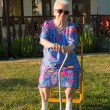 Old woman sitting on a chair with a cane — Stock Photo
