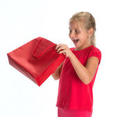 Exciting little girl looking inside shopping bag — Stock Photo