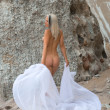 Nude woman on the beach with white cloth — Stockfoto