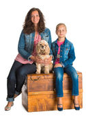 Mother and daughter sitting in a wooden chest with american span — Stock Photo