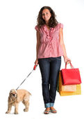 Curly woman with shopping bags and american spaniel — Stock Photo