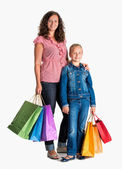 Smiling mother and daughter with shopping bags — Stock Photo