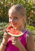 Little girl tasting watermelon — Stock Photo