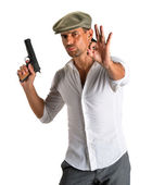 Handsome man in cap with a gun — Stock Photo