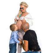 Mulher grávida com o marido e o filho dela beijando sua barriga — Foto Stock