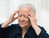 Senior woman suffering from headache — Stock Photo