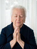 Senior woman praying — Stock Photo