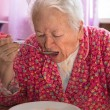 Senior woman eating soup — Stock Photo