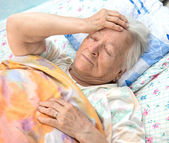 Old sick woman lying at bed — Stock Photo