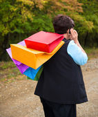 Woman talking on the phone and holding shopping bags — Stock Photo